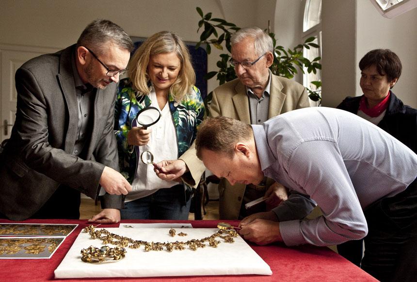 kustorz i badacze oglądają złotą koronę