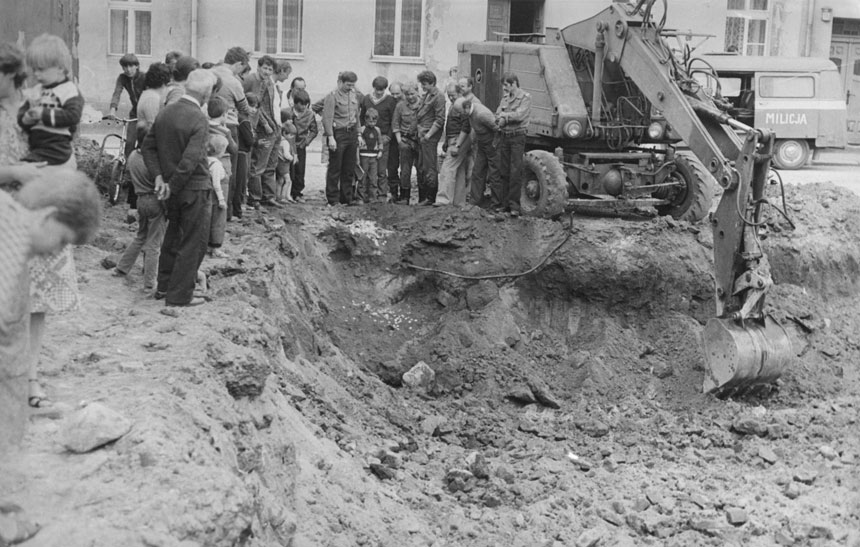 koparka z odkopanym skarbem i ludzie patrzący na znalezisko