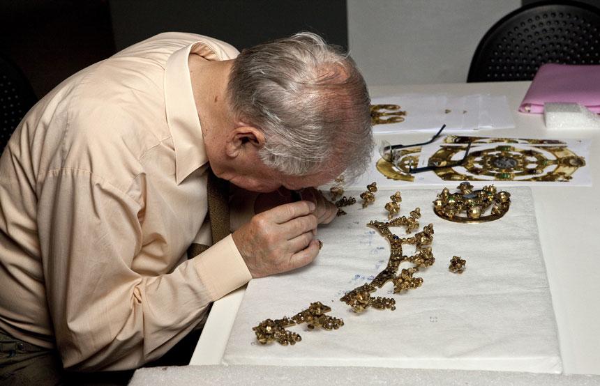 specjalista ogląda fragmenty korony przez szkło powiększające