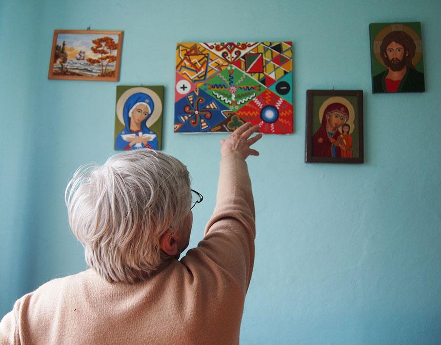 artystka pokazuje wiszące na ścianie obrazki