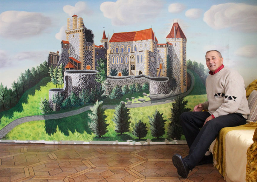artysta siedzi obok malowidła przedstawiającego średniowieczny zamek