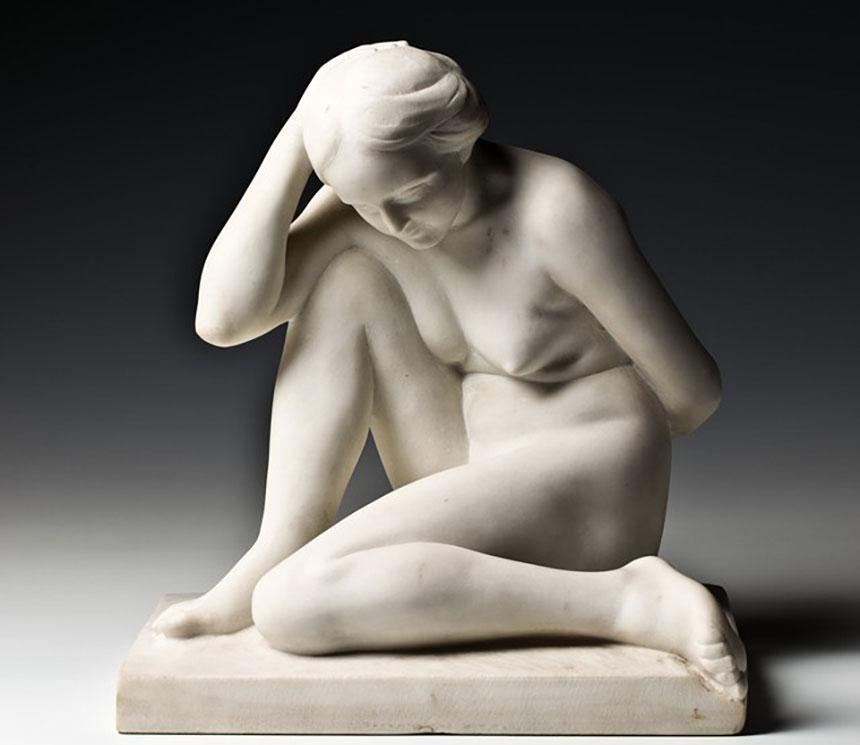 biała rzeźba siedzącej nagiej kobiety