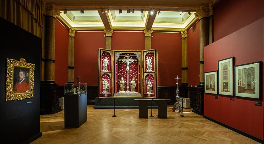 """prezentacja fragmentu wystawy """"Dwa ołtarze"""" – srebrny ołtarz Jerina naplanie głównym (krzyż, dwie klęczące postaci, naskrzydłach święci – srebrno-złoci. tło atłasowe, bordowe"""