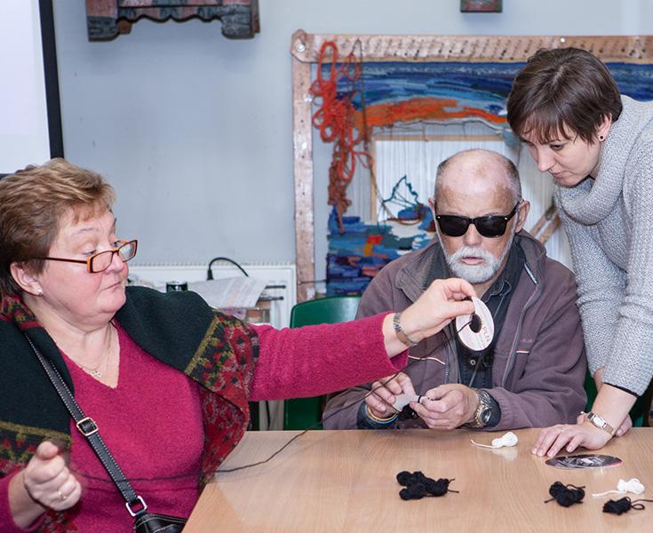 po lewej pani w okularach i w czerwonym swetrze i ciemnej chuście przeplata włóczkę, obok stojąca po prawej stronie dziewczyna pomaga panu w ciemnych okularach