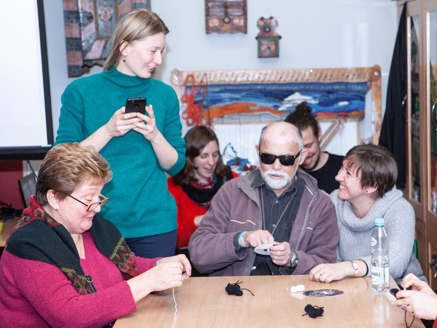 Dusiołki – zajęcia z robienia pomponów z włóczki – uczestnicy siedzą wokół stołu, dziewczyna stoi przy panu w ciemnych okularach