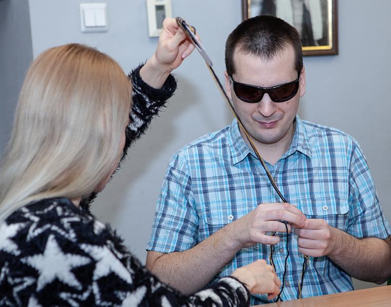 Zajęcia z robienia pomponów – ciąg dalszy – dziewczyna pomaga chłopakowi w okularach przewlec nitkę