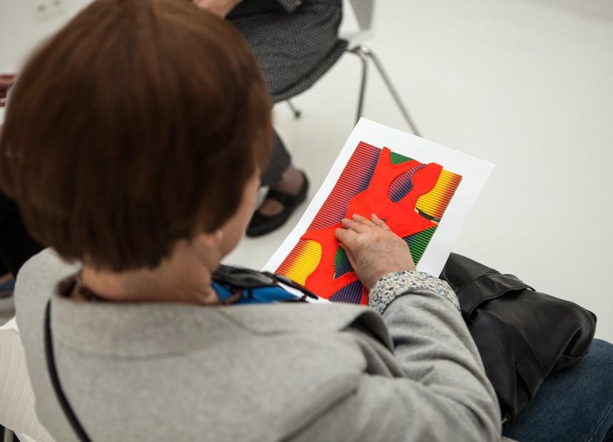 siedząca pani trzyma dłoń na kolorowej grafice