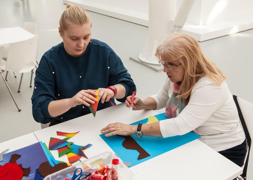 dwie uczestniczki tworzą pracę z kolorowych fragmentów