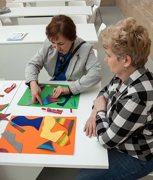 kolejne dwie uczestniczki tworzą pracę z kolorowych fragmentów