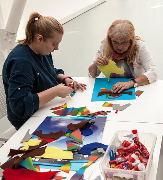 inne ujęcie dwóch pań, które z kolorowych fragmentów obrazków układają swoje prace
