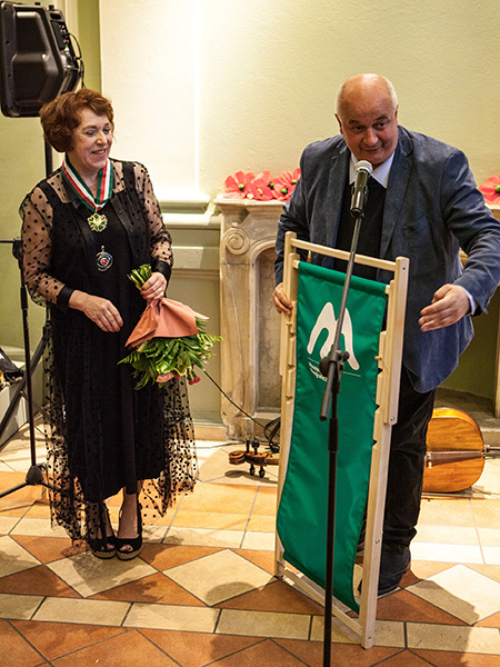 dyrektor Muzeum wręcza pani kierownik prezent jubileuszowy w postaci zielonego leżaka