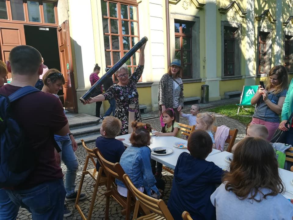 pani Paulina pokazuje dzieciom deszczownicę z tuby – instrument grający