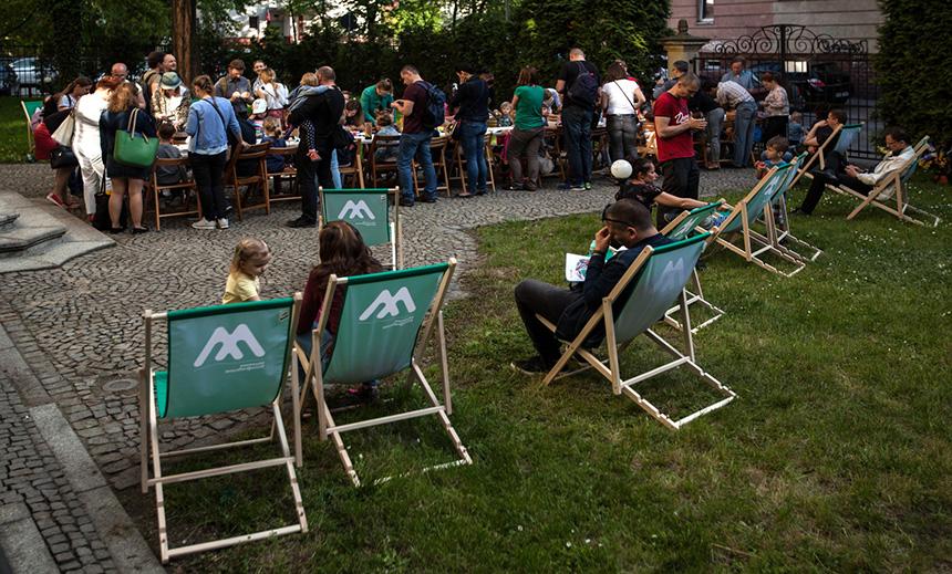 dzieci siedzią na leżakach w ogrodzie przy muzeum, w tle inne dzieci przy stołach mają warsztaty