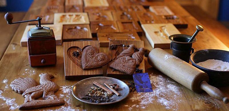 drewniane foremki rzeźbione doodciskania ozdobnych pierników, obok wałek, młynek, moździerz, talerz zcynamonem, goździkami iinnymi przyprawami orazmiska zmąką