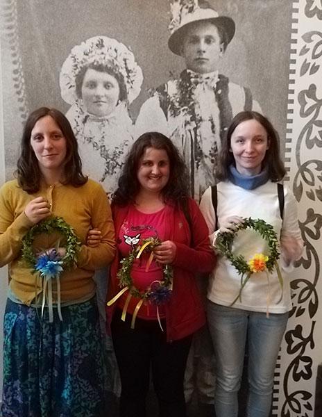 trzy dziewczęta trzymają wianki, stoją na tle portretu państwa młodych w ludowych strojach