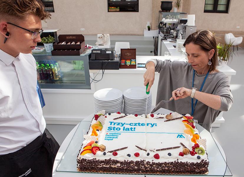 krojenie tortu z napisem Trzy-cztery: Sto lat!