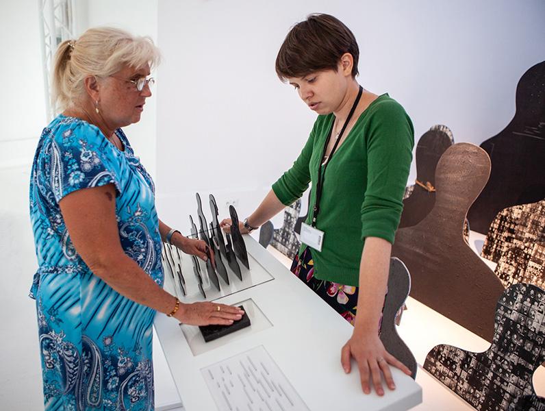 prowadząca wraz zuczestniczką dotykiem poznają prace Szajny natyflografice
