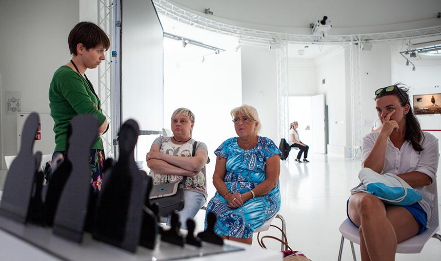 rozmowa przy rzeźbach, prowadząca stoi, uczestnicy siedzą