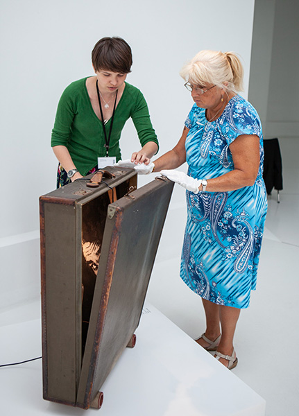 prowadząca iuczestniczka zajęć otwierają wielką walizkę