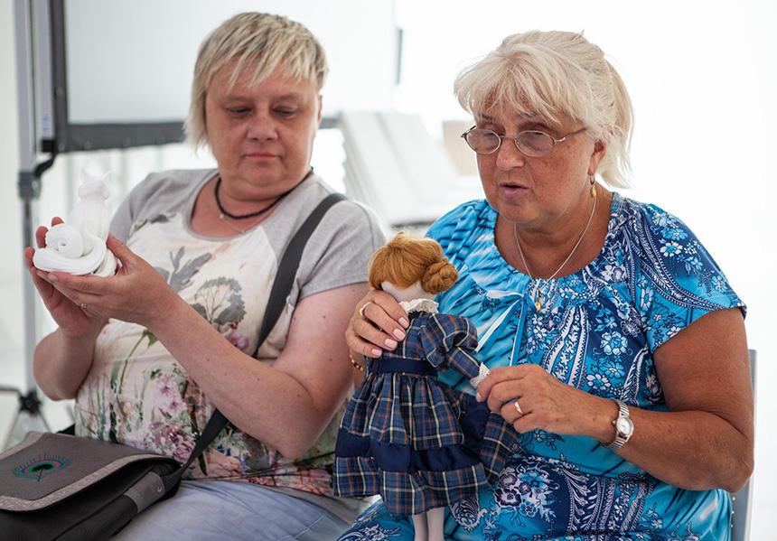 uczestniczka zajęć ogląda palcami porcelanową lalkę wgranatowej sukience wkratkę
