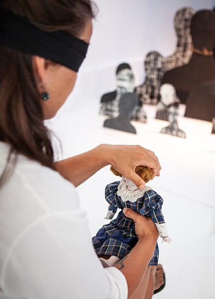inna uczestniczka zzawiązanymi oczami również ogląda lalkę palcami