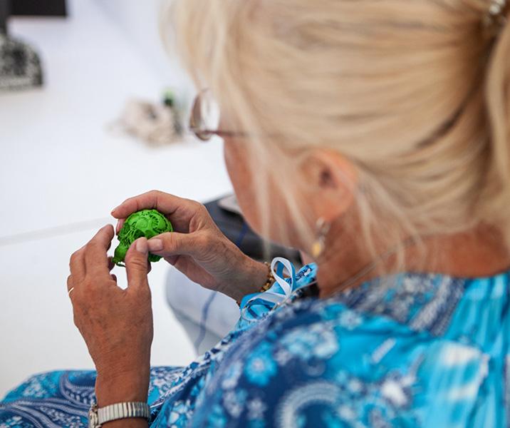 dotykanie zielonej plastikowej czaszki stylizowanej wmeksykańskie wzory