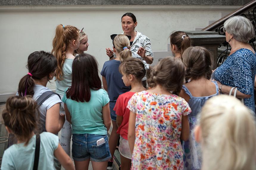Dzieci otaczają panią prowadzącą i słuchają jej wykładu