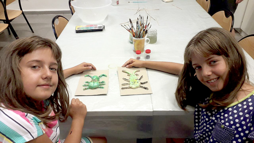 dwie dziewczynki prezentują ulepione przezsiebie owady sześcionożne zczułkami