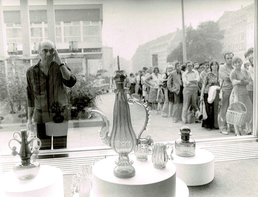 archiwalne zdjęcie zza witryny widać stojących ludzi wkolejce podsklepem