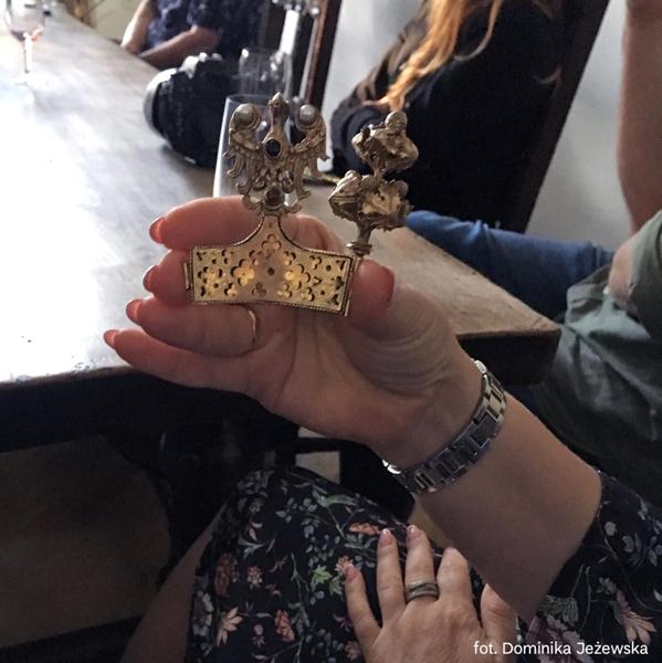 uczestniczka oprowadzania trzyma wręku fragment repliki złotej korony