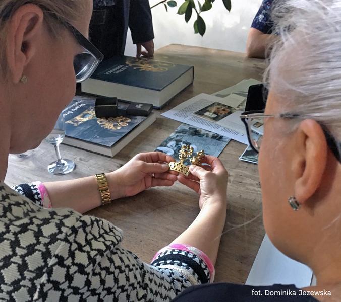 uczetniczki przyglądają się złotemu fragmentowi korony