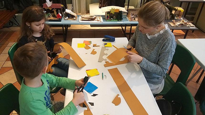 fotorelacja zzajęć – dzieci przy stołach ozdabiają wycięte zżółtego kartonu korony, apotem je przymierzają