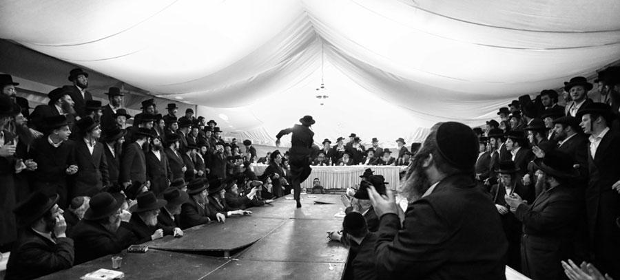 tańczący chasyd w grupie śpiewających