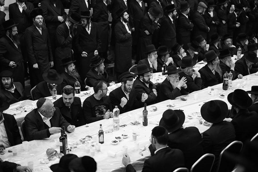 chasydzi siedzący przy długich stołach, śpiewający lub modlący się