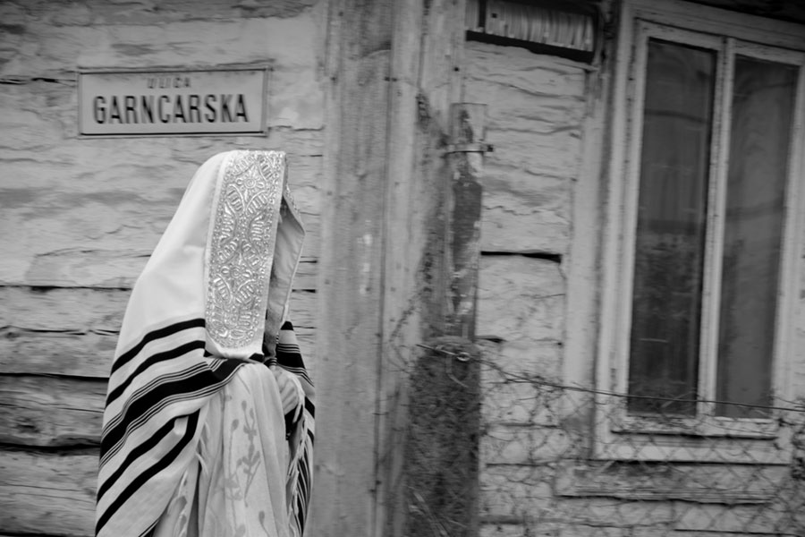 idący modlący się chasyd okryty modlitewną tkaniną, w tle drewniana chata z napisem ulica Garncarska