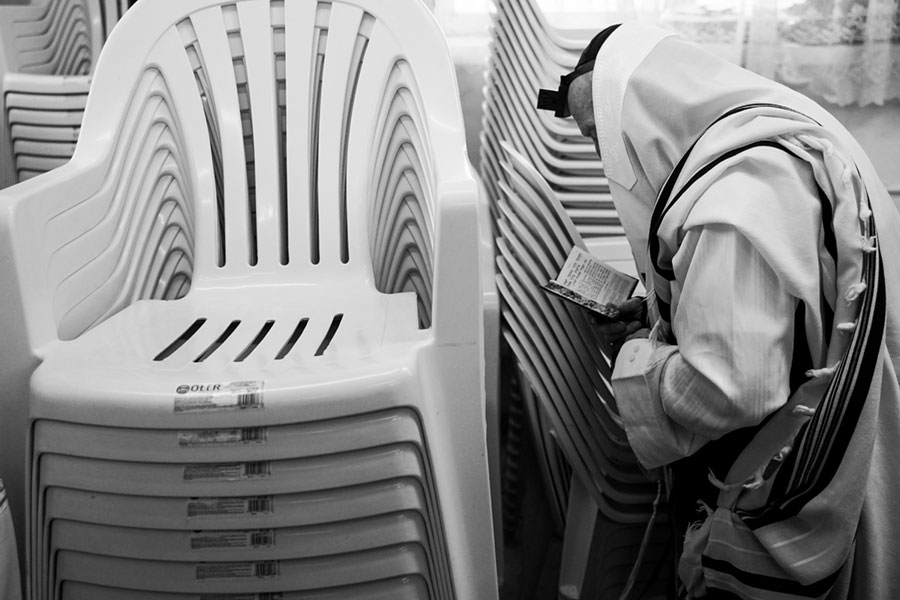 modlący się przy białych krzesłach chasyd