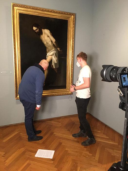 fotorelacja znagrywania: kamerzysta idyrektor muzeum spoglądają nadetal obrazu Zubarana