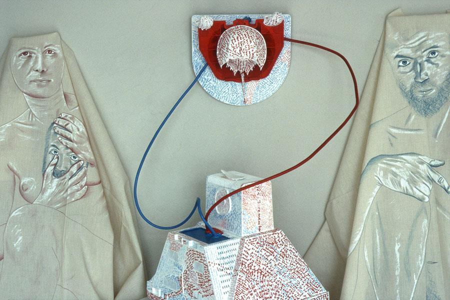chusty nakrzesłach zmalunkami kobiety imężczyzny, wśrodku czerwono-niebieski element łączący