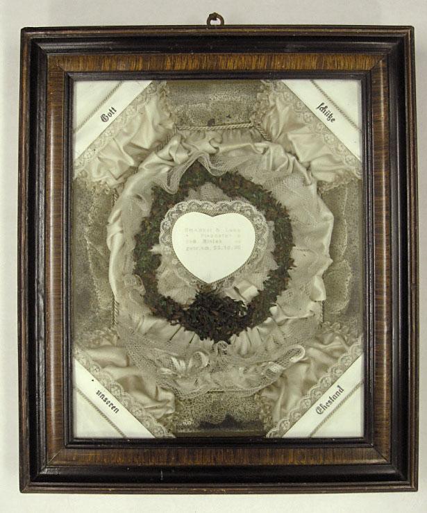 ozdoba wramce podszkłem, wśrodku ozdobione koronkami biale serce, poniżej wkoronkach gałązki mirtowe