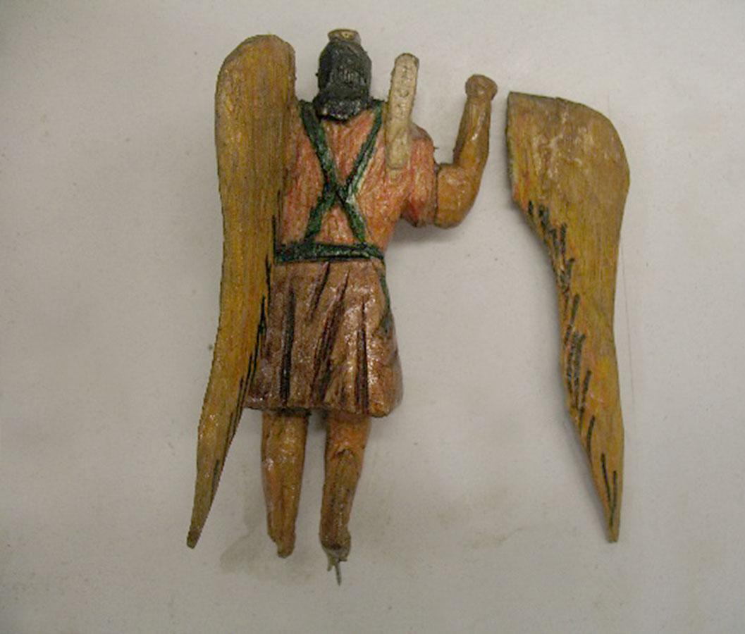 mała rzeźba archanioła zodłamanym skrzydłem, widziana odtyłu
