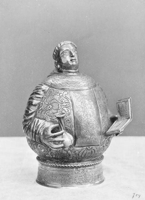 mnich zokrągłych brzuszkiem, trzyma buteleczkę iksięgę