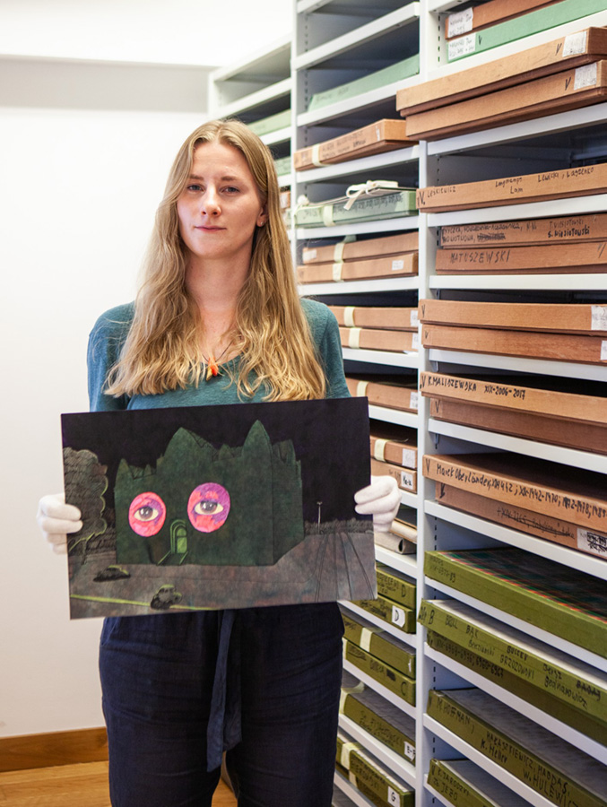 Kuratorka prezentuje grafikę natle muzealnych półek